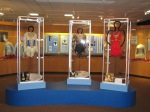 In the back left case, exhibition costumes worn by 1977-1980 U.S. pair champions and two-time Olympians Tai Babilonia and Randy Gardner. Pictured in the center are Tara Lipinski's short program costume and gold medal from the 1998 Olympics, Kristi Yamaguchi's free skate costume and gold medal from the 1992 Games (both Tara and Kristi's dresses were designed by Lauren Sheehan) and Michelle Kwan's free skate costume from 2002 (designed by Vera Wang). The case on the right in back has exhibition costume worn by Cecilia Colledge, British champion, 1936 Olympic silver medalist and 1937 world champion. Not pictured is Scott Hamilton's gold medal winning costume from 1984 along the near wall.
