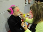 Coach Nadine Lewis applies makeup to her skater Zazi Ebert Byrnes of the All Year FSC.